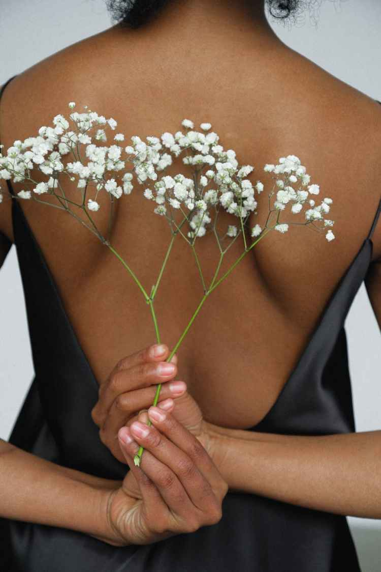 close up photo of woman in black night dress holding white flower behind her back